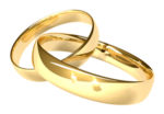 Two linked gold rings.  Two candles reflected in the gold.  Shallow depth of field.